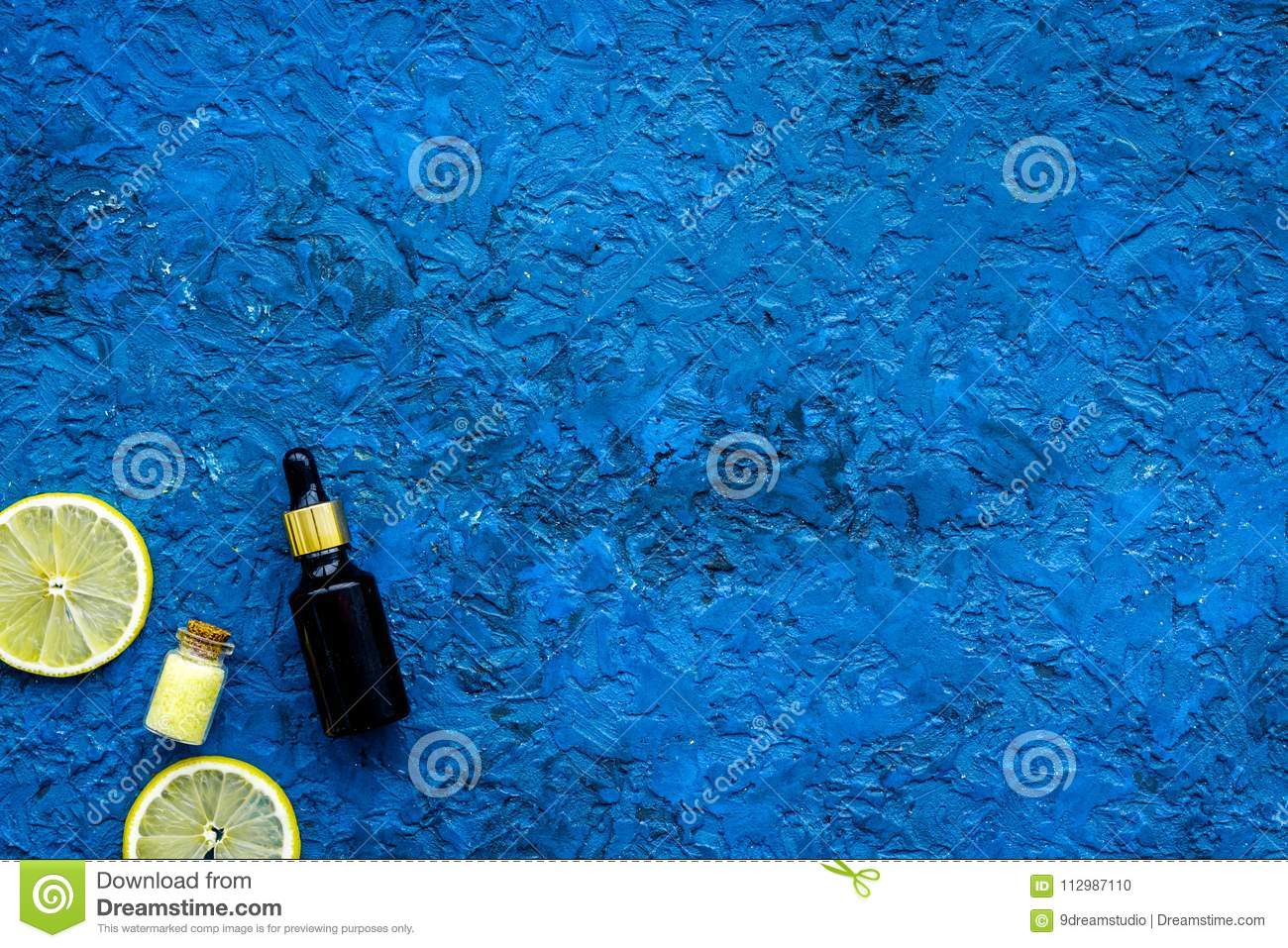 Organic cosmetic with lemon for homemade spa with oil and fresh fruit blue background top view mock up