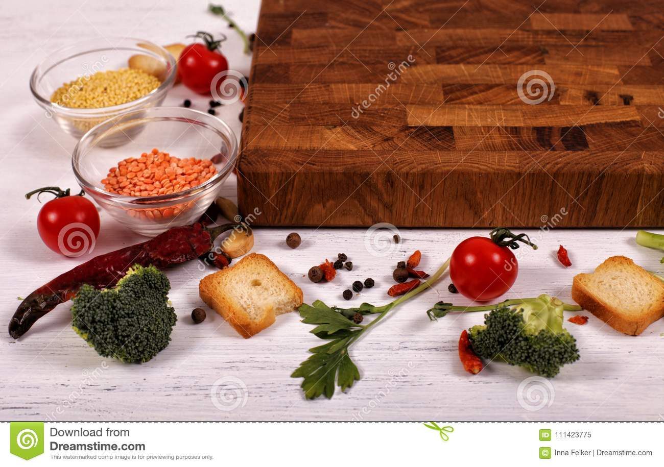 Organic food with empty brown cutting board on white wooden table.