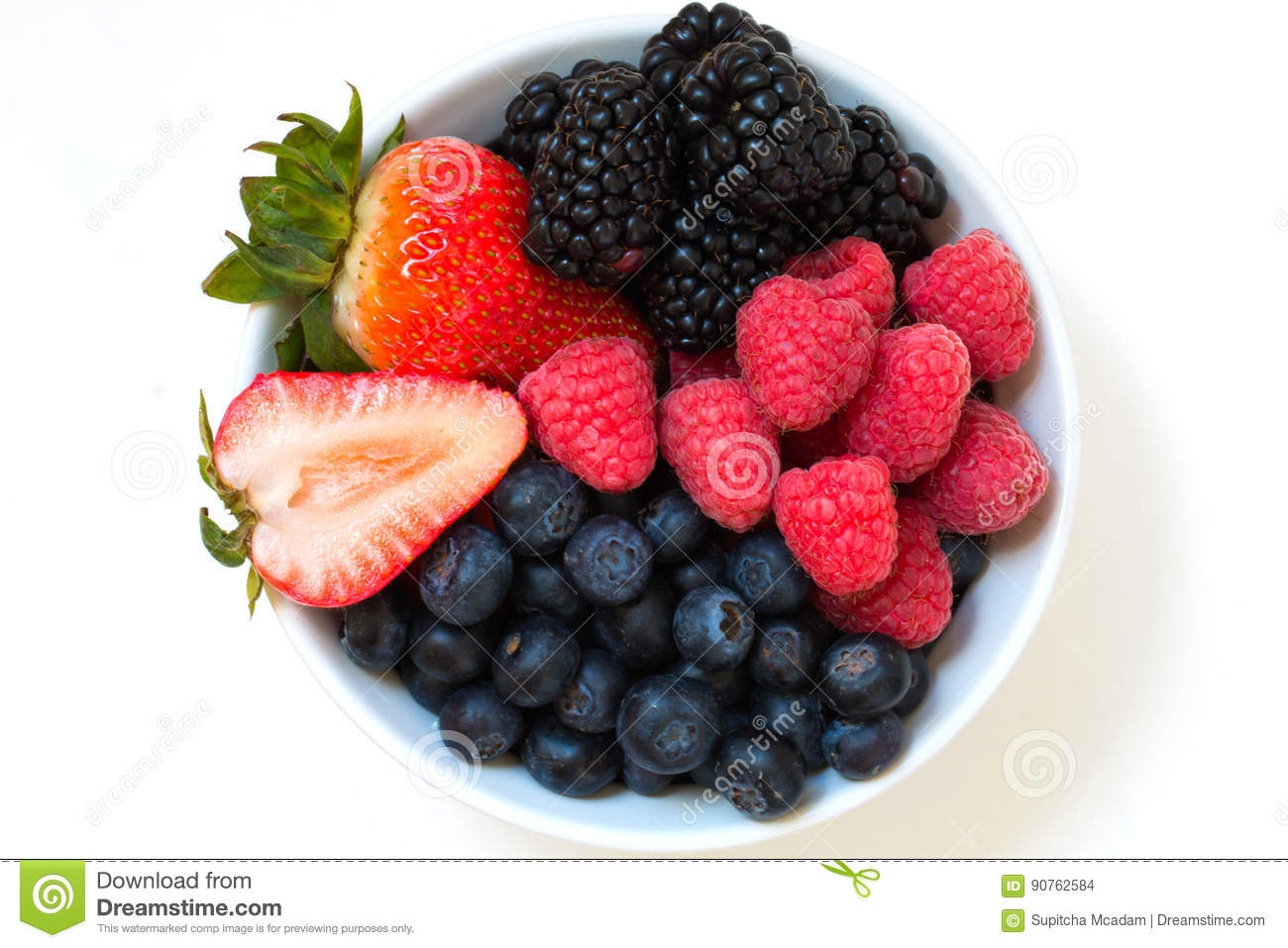 Organic fresh mixed berries fruit in a bowl on the table.