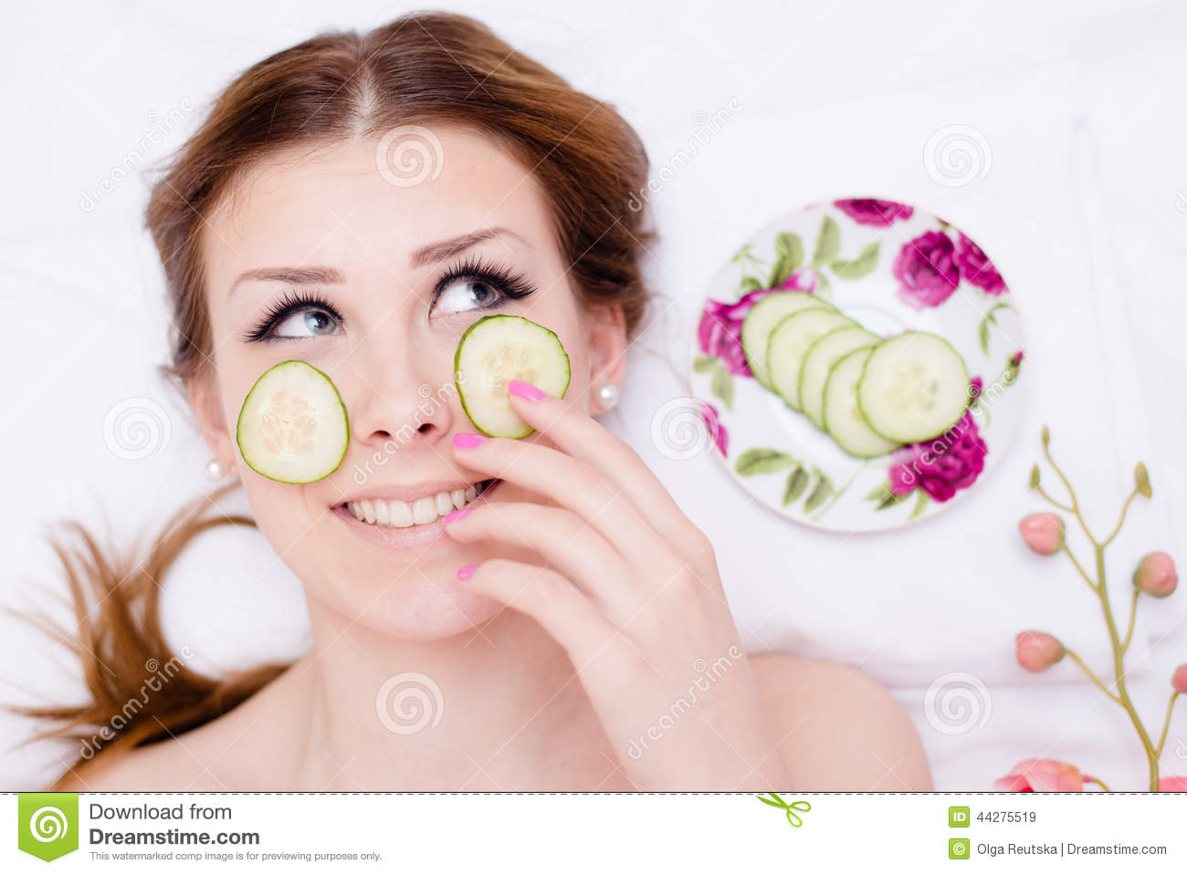 Organic green natural spa treatment: happy beautiful blond young lady having fun applying slices of cucumber to her face skin