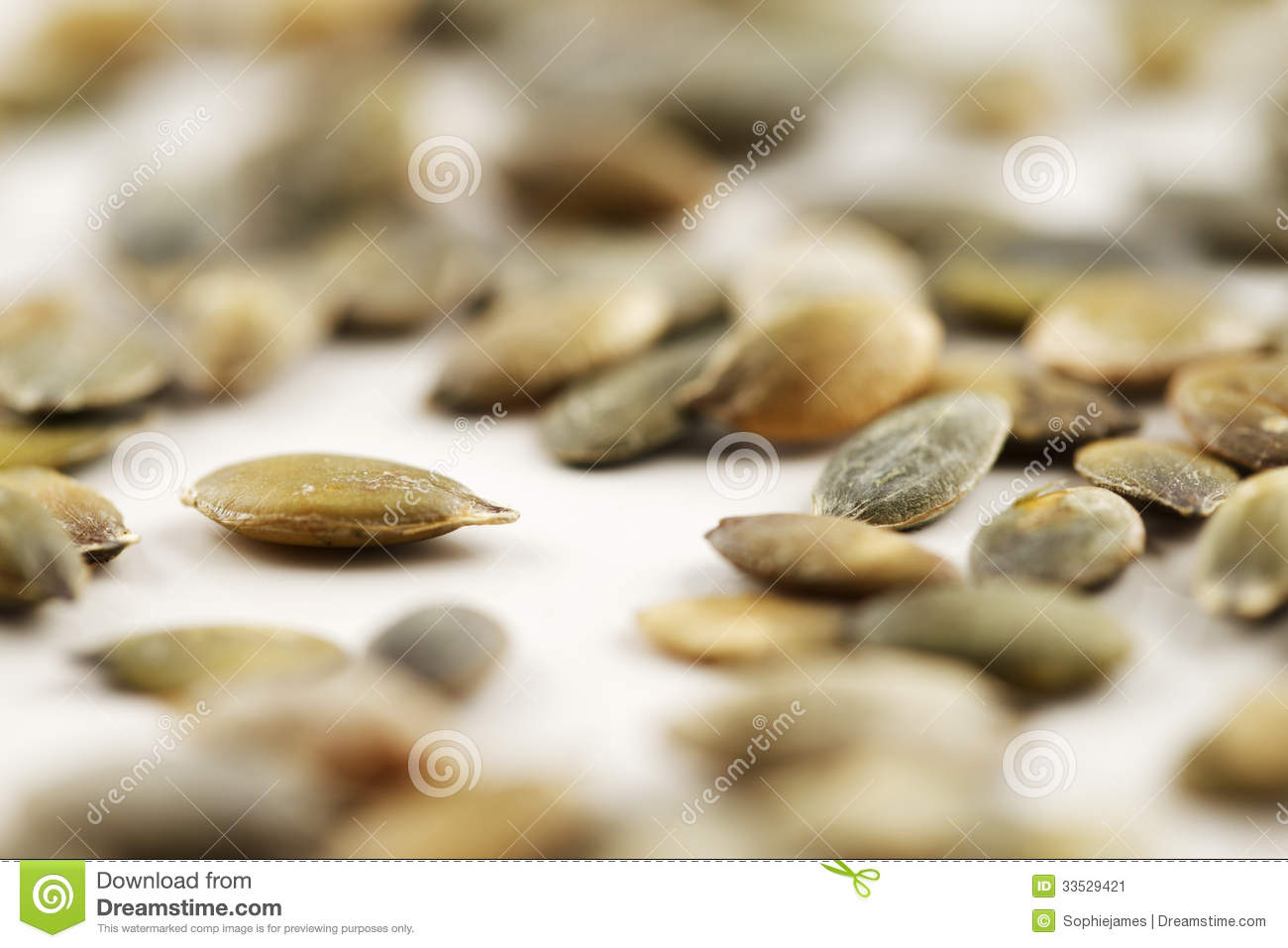 Organic green pumpkin seeds against a white background