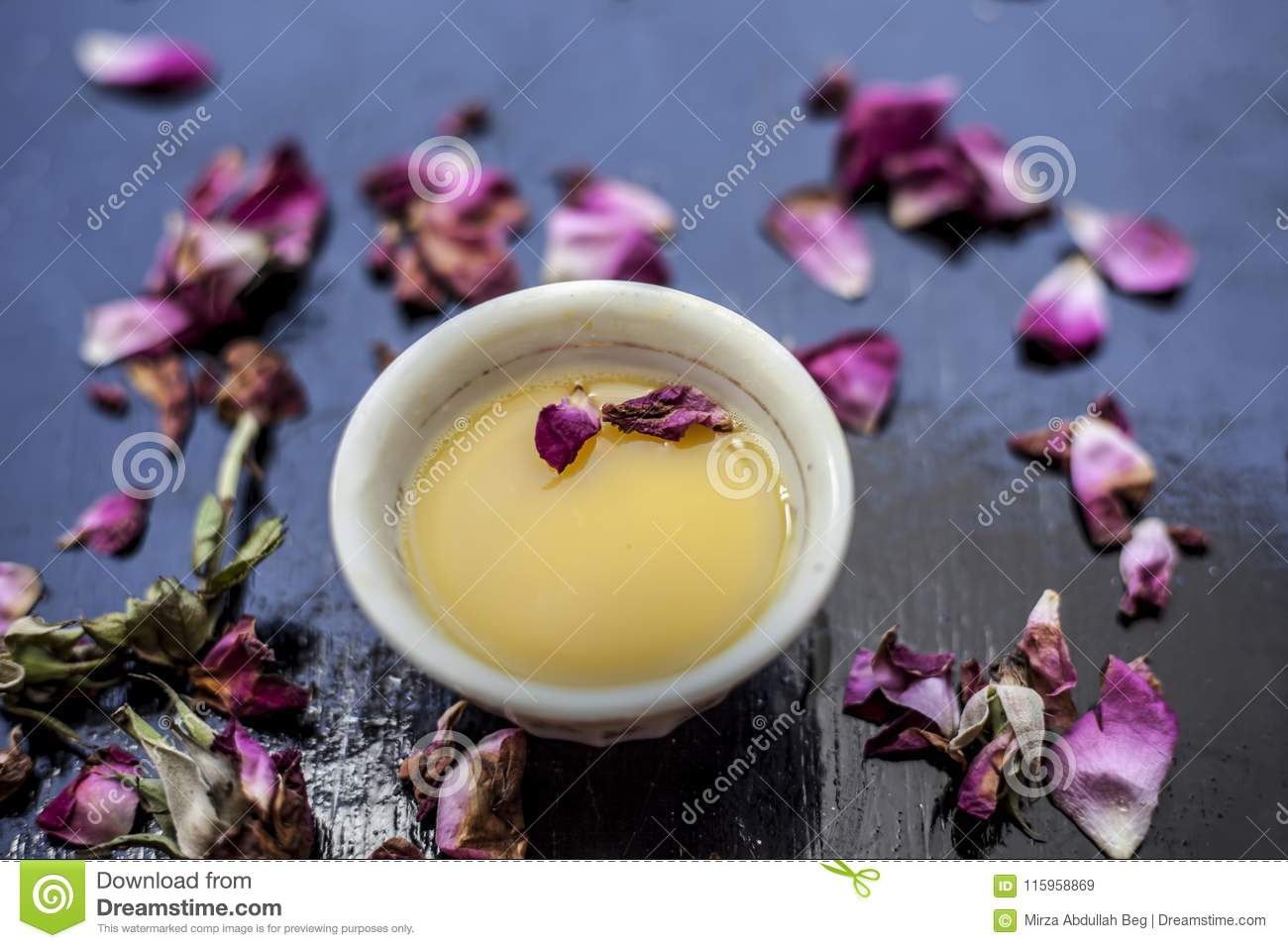 Organic and herbal face pack of Honey & Gram flour with its thick liquid mixture and some rose petals for good aroma on wooden sur