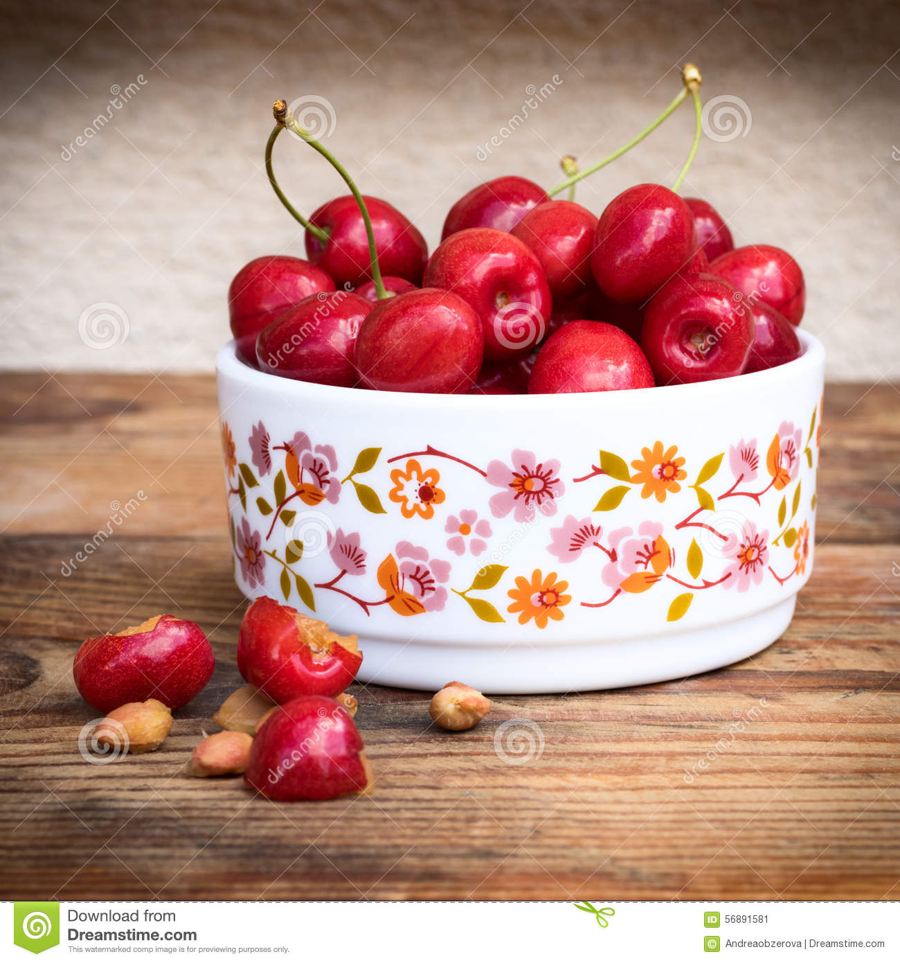 Organic homegrown cherries and stones in a vintage ceramic bowl, on wooden background