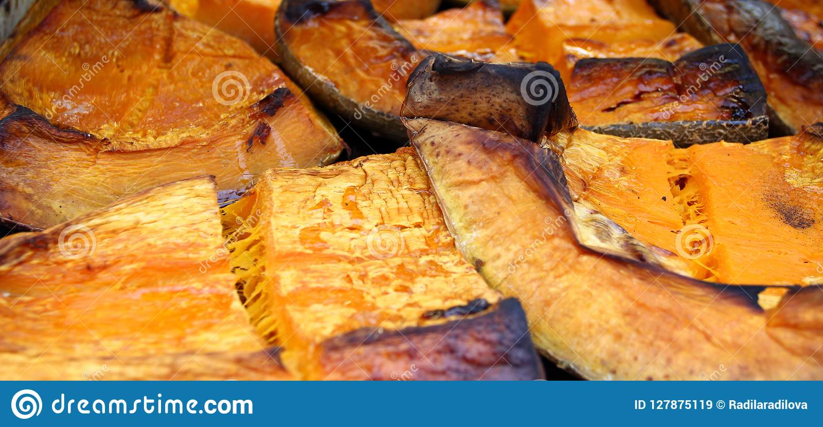 Organic Pumpkin slice baked for Halloween holiday. Colorful baked squash background. Pumpkin texture pattern. Sweet Grilled pumpki