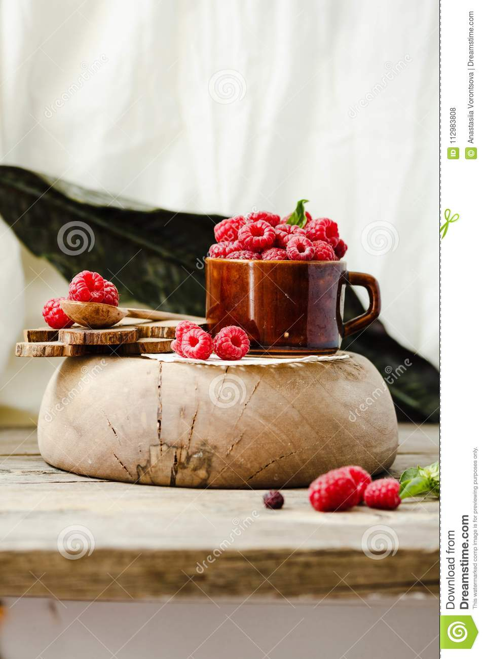Organic raspberry with basil in a cup of coffee and a wooden sta