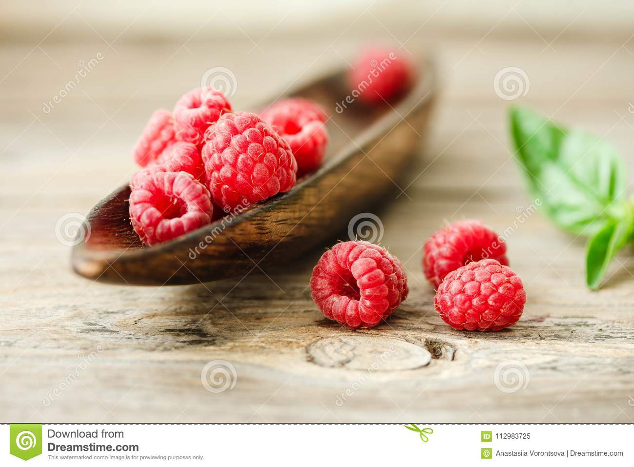 Organic raspberry sweet raspberry and green basil in a wooden pl