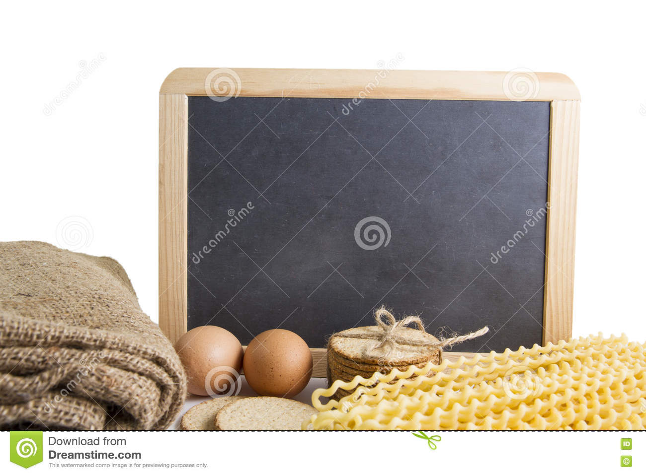 Organic yellow long pasta spirals and egg with black board background for text