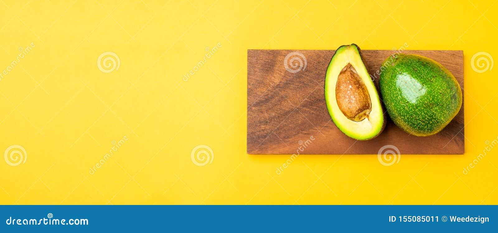 Organicznie avocados połówki cięcie z nasieniodajną i całą owoc na drewnianej tacy na koloru żółtego stołu tle Zdrowi super foods