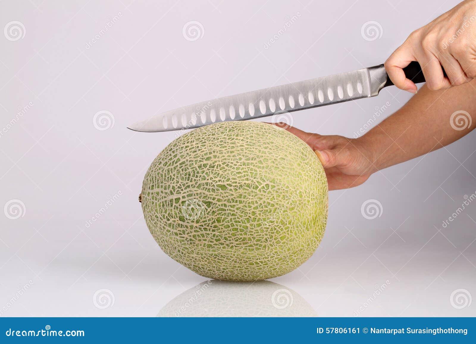 Organicznie kantalupa melonowa owoc z kuchennym nożem w ręki isolat