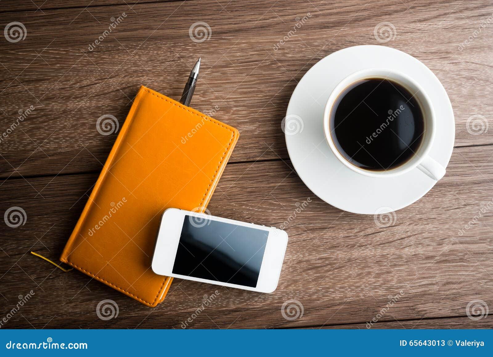 Organisateur avec la tasse du café et du téléphone portable