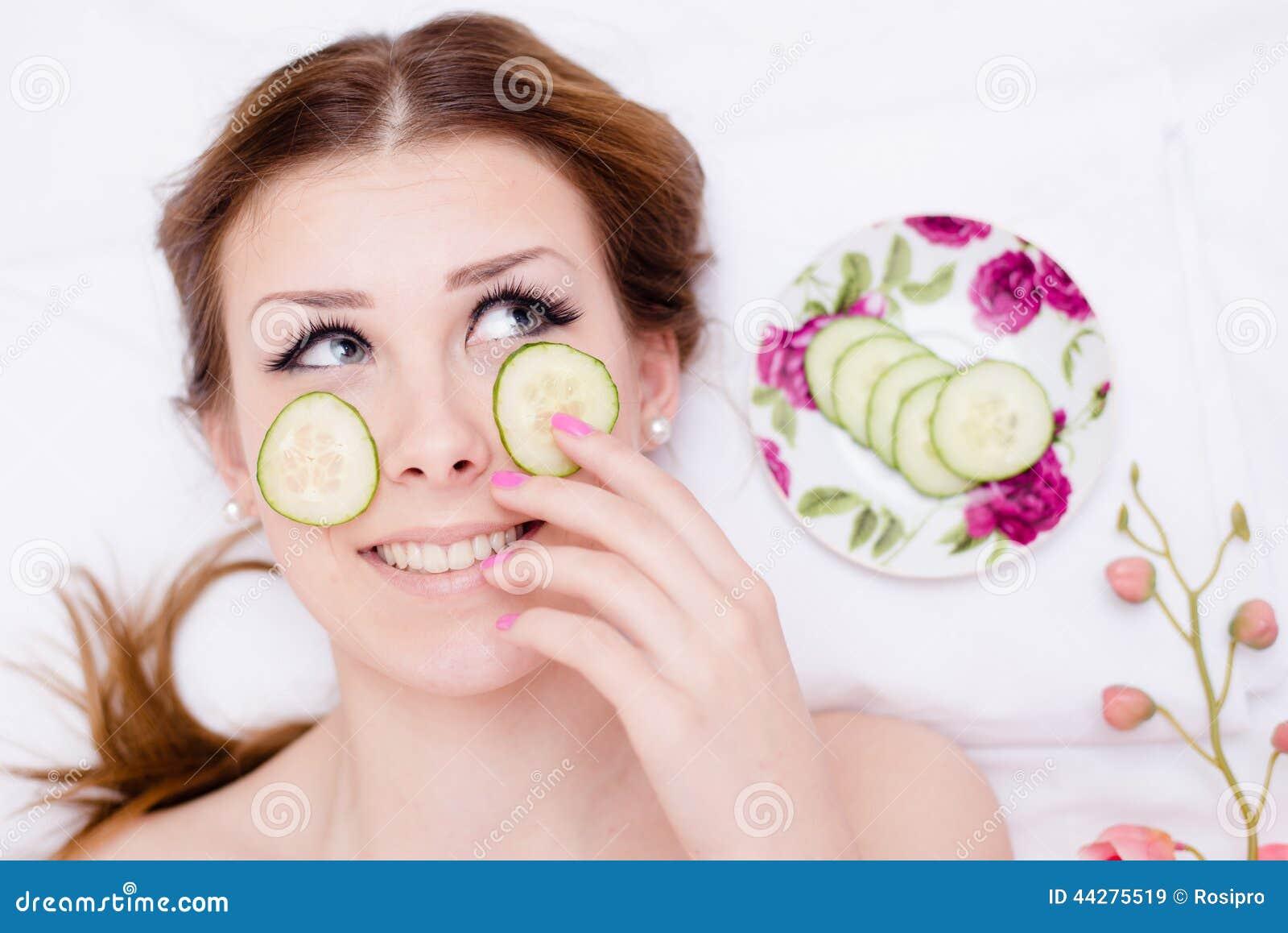 Organische groene natuurlijke kuuroordbehandeling: gelukkige mooie blonde jonge dame die pret hebben die plakken van komkommer to