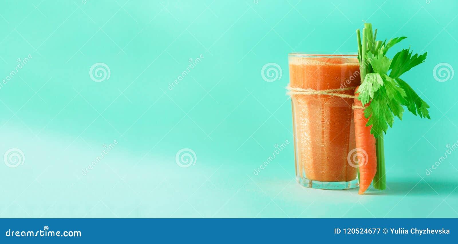 Organischer Karottensaft mit Karotten, Sellerie auf blauem Hintergrund Frischgemüse smothie im Glas fahne Kopieren Sie Platz