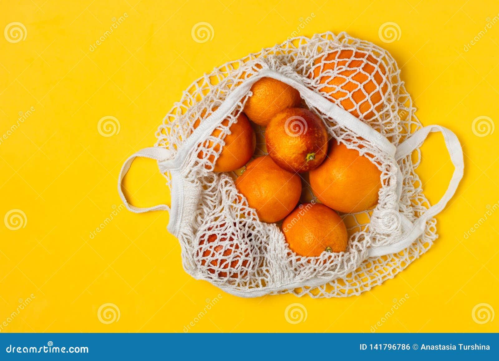 Organiska blodiga apelsiner i den återvinningsbara påsen för bomullsingrepp, gul bakgrund - återanvända, hållbar livsstil, nollav