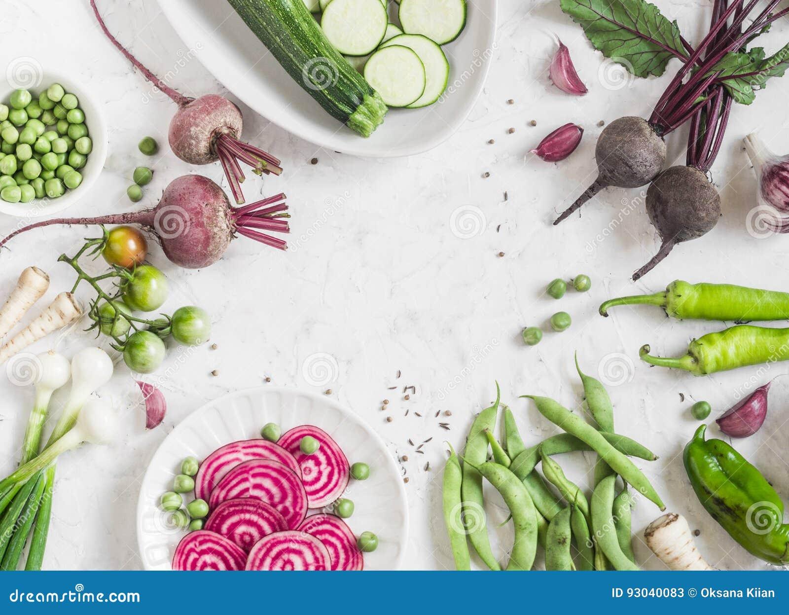 Organiska purpurfärgade och gröna grönsaker på en vit bakgrund Detoxingredienser Sunt vegetariskt matbegrepp Bästa sikt, fri brun