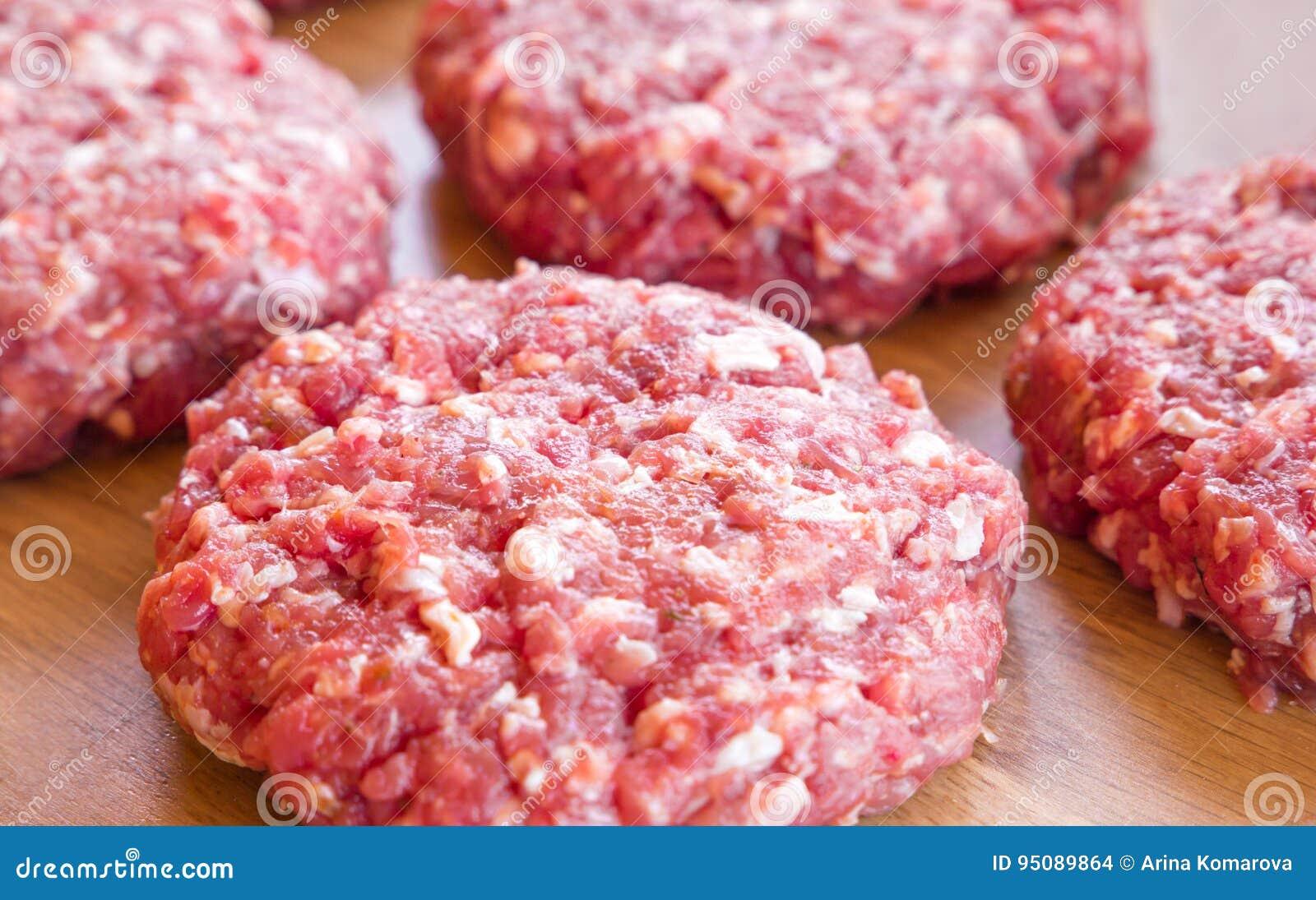 Organiskt rått jordnötkött, runda små pastejer för framställning av den hemlagade hamburgaren på träskärbräda