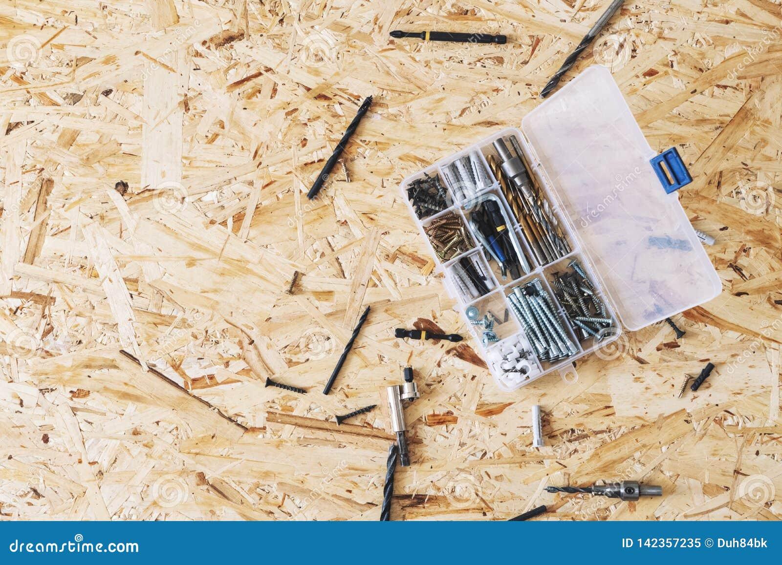 Organizador transparente plástico com parafusos, passadores, brocas, bocados no fundo do OSB