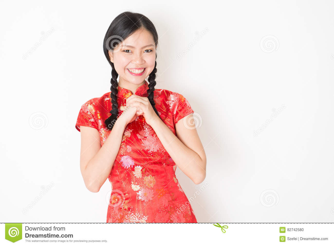 cc6ac299c Portrait of young Asian girl in traditional qipao dress smiling and  greeting, celebrating Chinese Lunar New Year or spring festival, standing  on plain ...