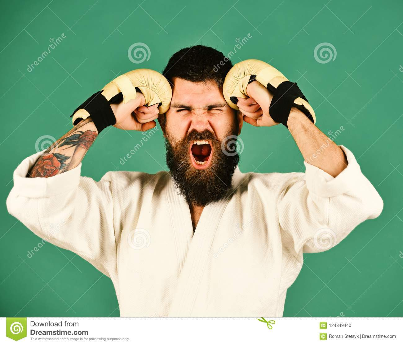 Oriental sports concept. Karate man with mad face in uniform