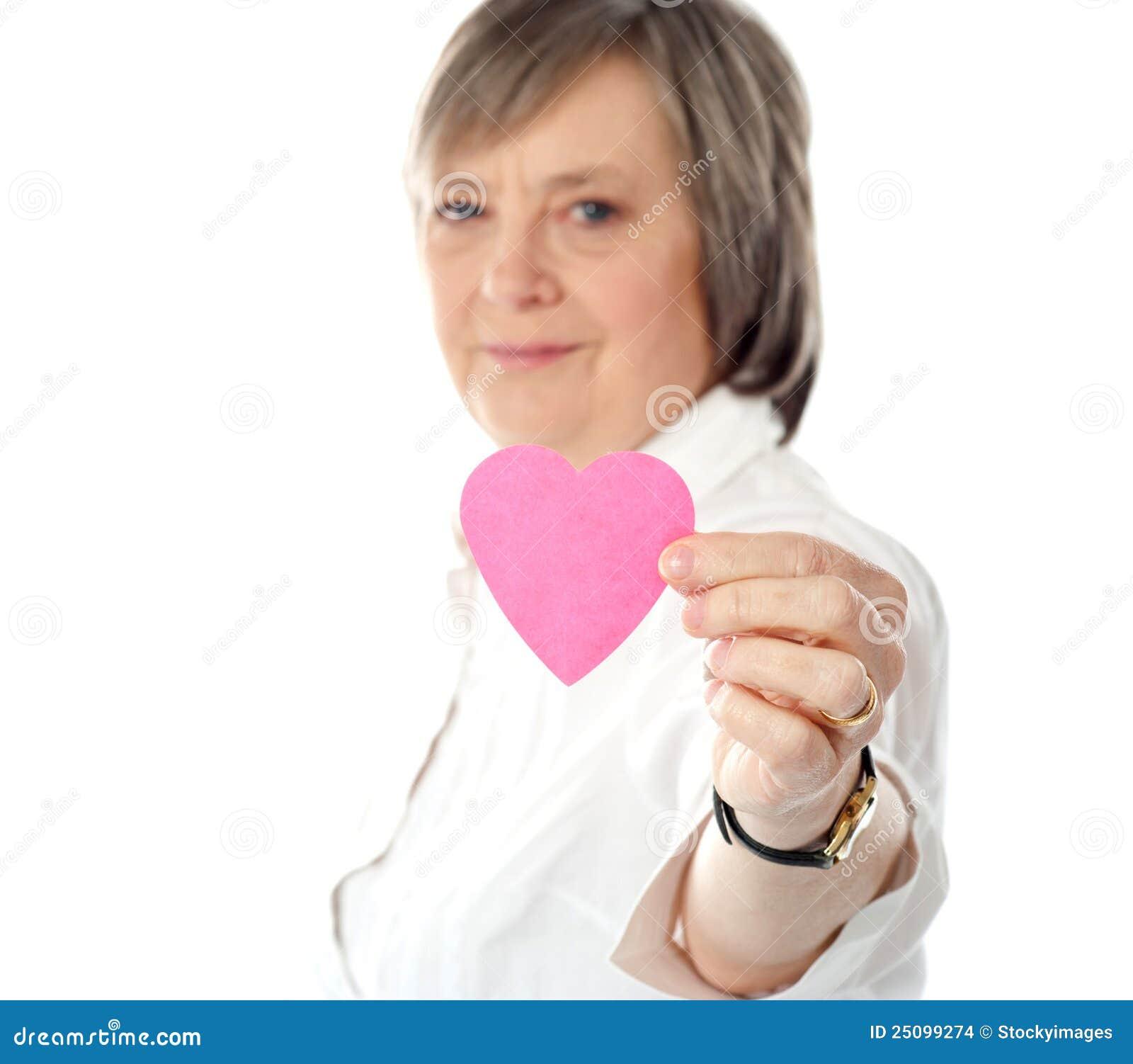 Orientation sur le coeur de papier rose. Fixation âgée de femme il