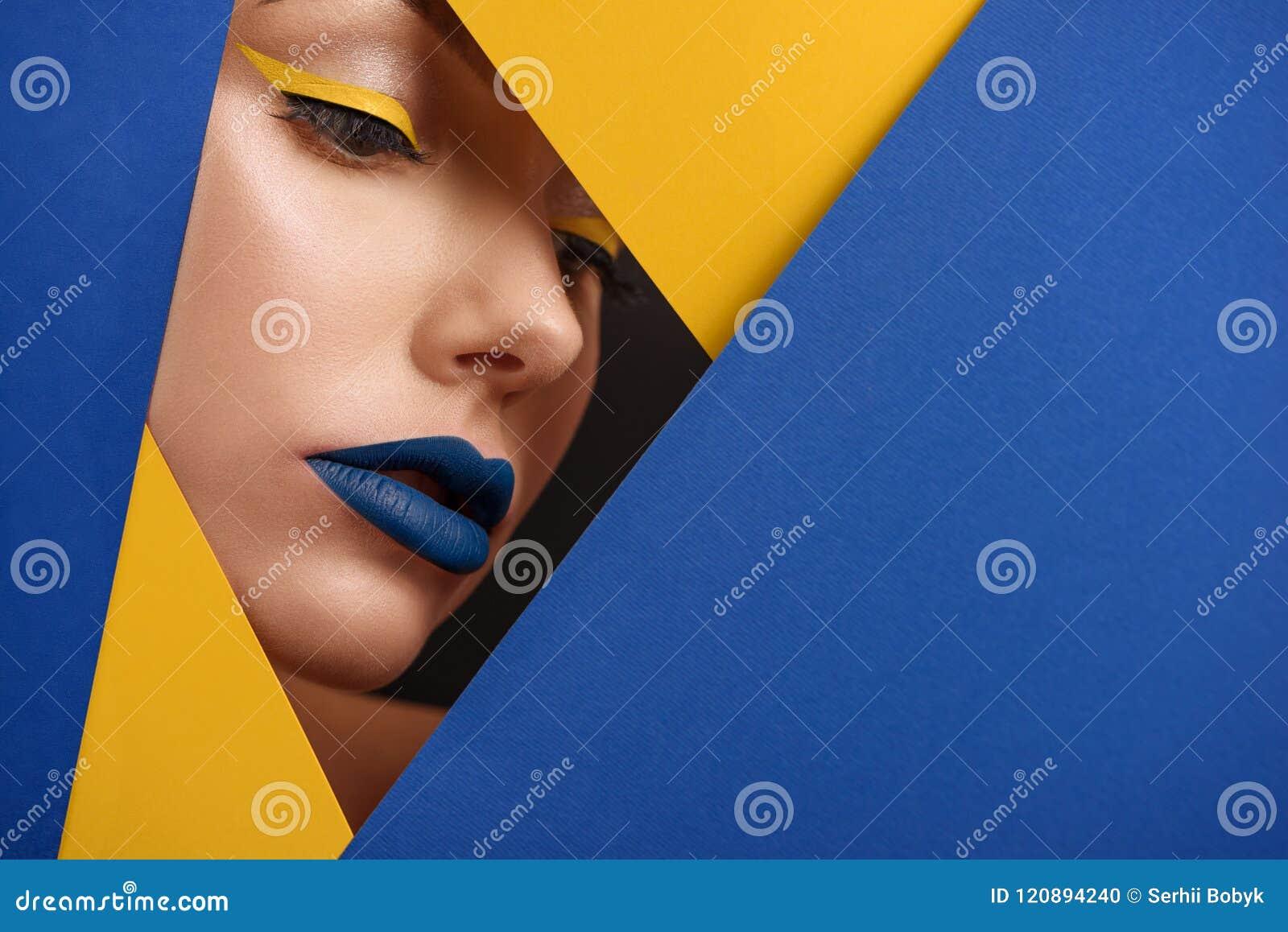 Originele beaty dichte omhooggaand van meisjes` s gezicht surronded door blauw en geel karton