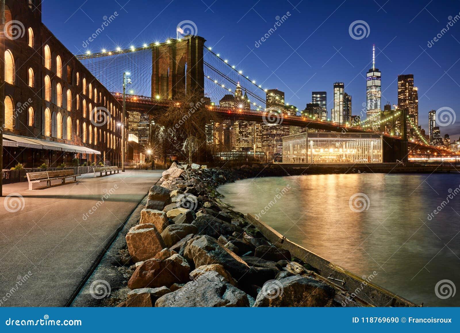 Orilla del río y Lower Manhattan del parque del puente de Brooklyn en el crepúsculo Brooklyn, Manhattan, New York City