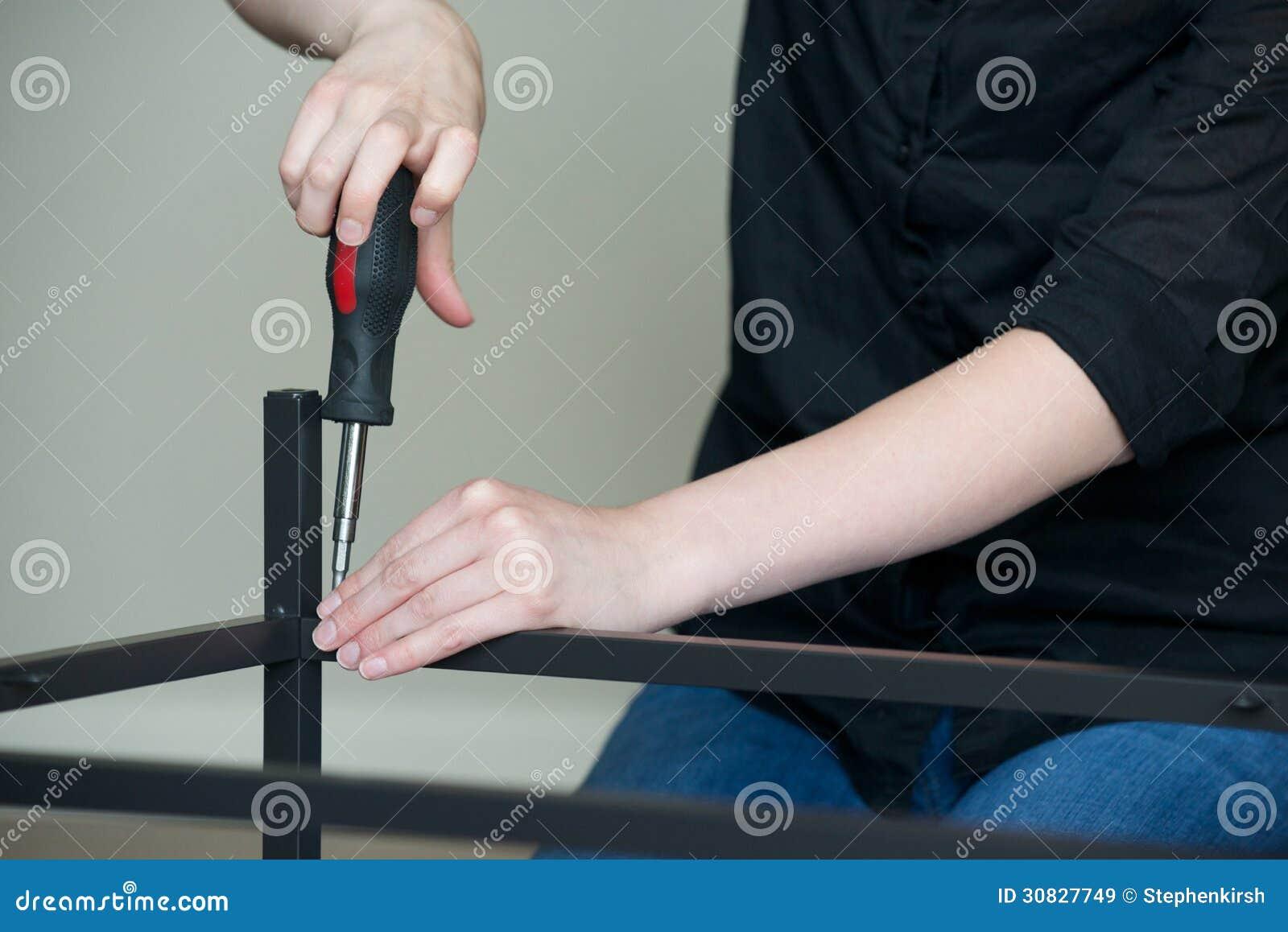 Orizzontale delle mani che avvitano insieme mobili metallici, sinistra ad angolo