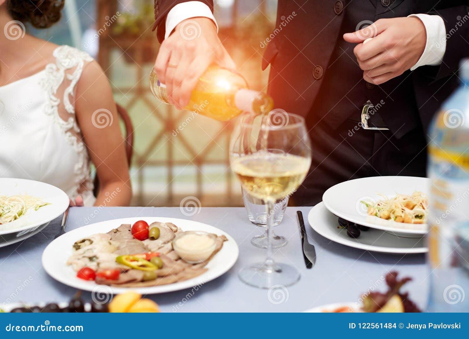 Orizzontale vicino su dell uomo caucasico in vino rosato di versamento della camicia bianca e del vestito nero in un vetro alto d