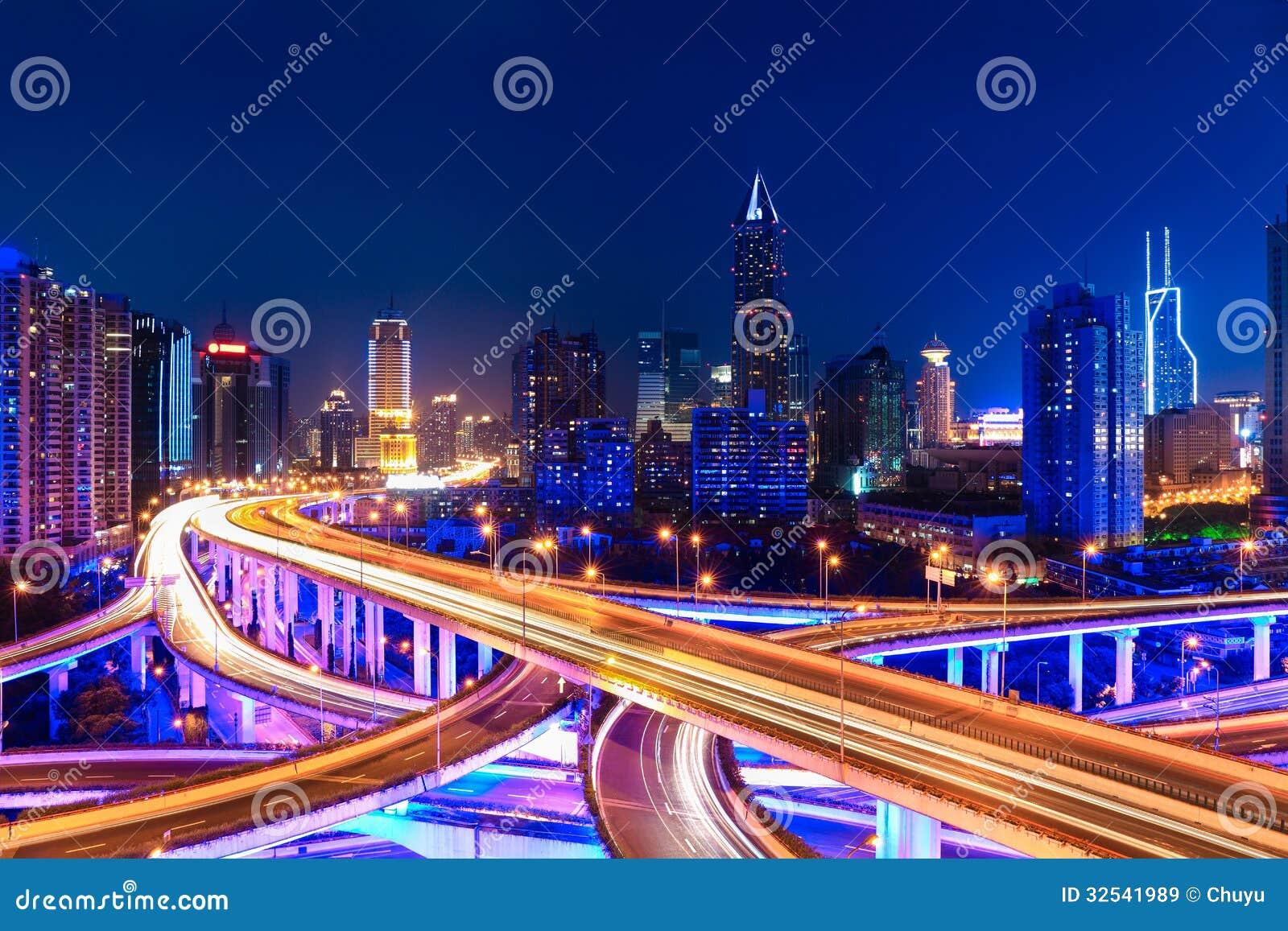 Orizzonte moderno della città con il passaggio di scambio alla notte