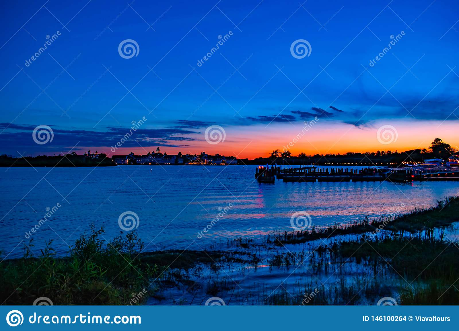 Panoramic view of Grand Floridian Resort & Spa and Magic Kingdom wharf on colorful sunset background at Walt Disney World area 6