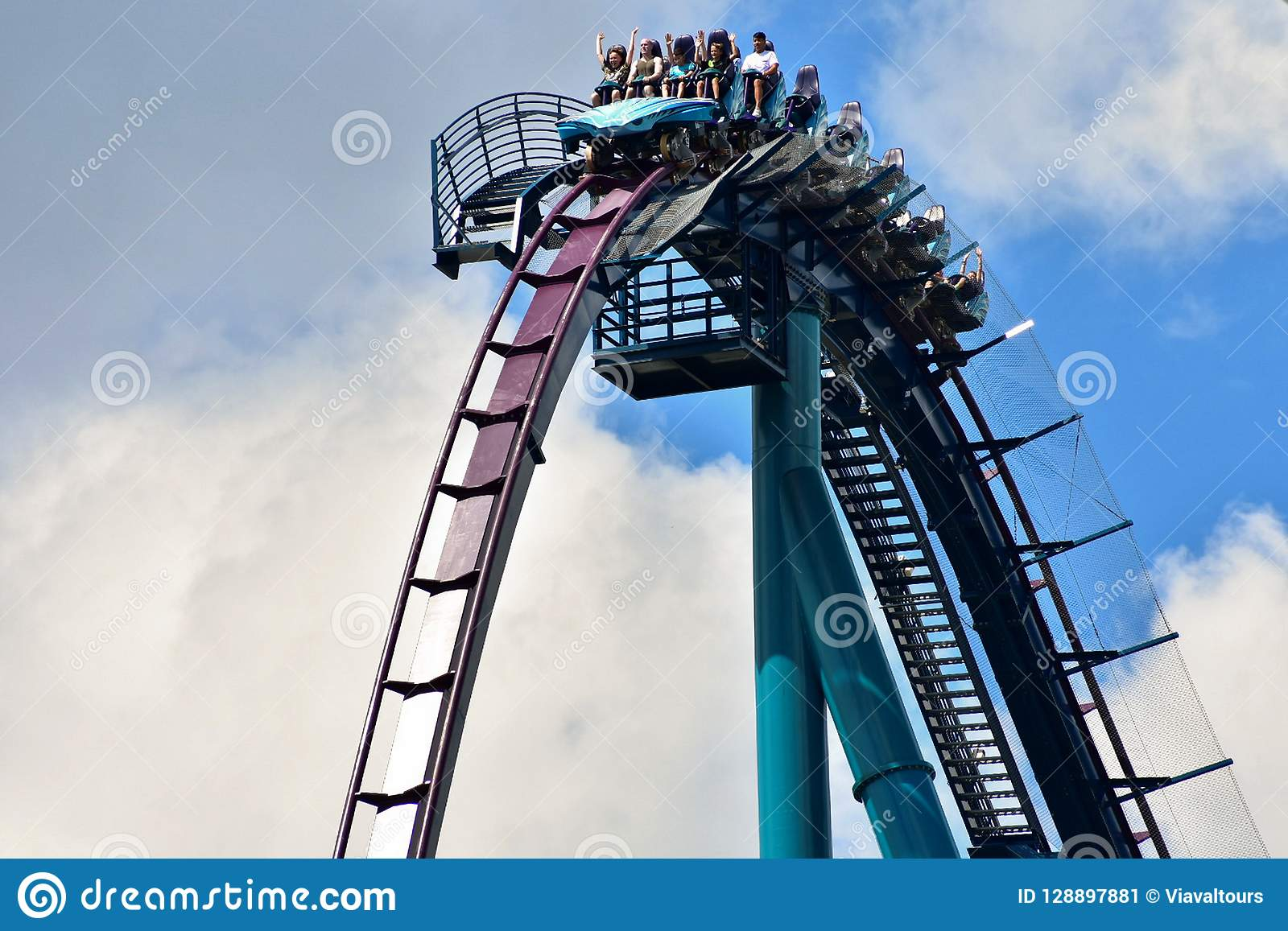 A Group of people enjoy a fast roller coaster ride located at International Drive Area.