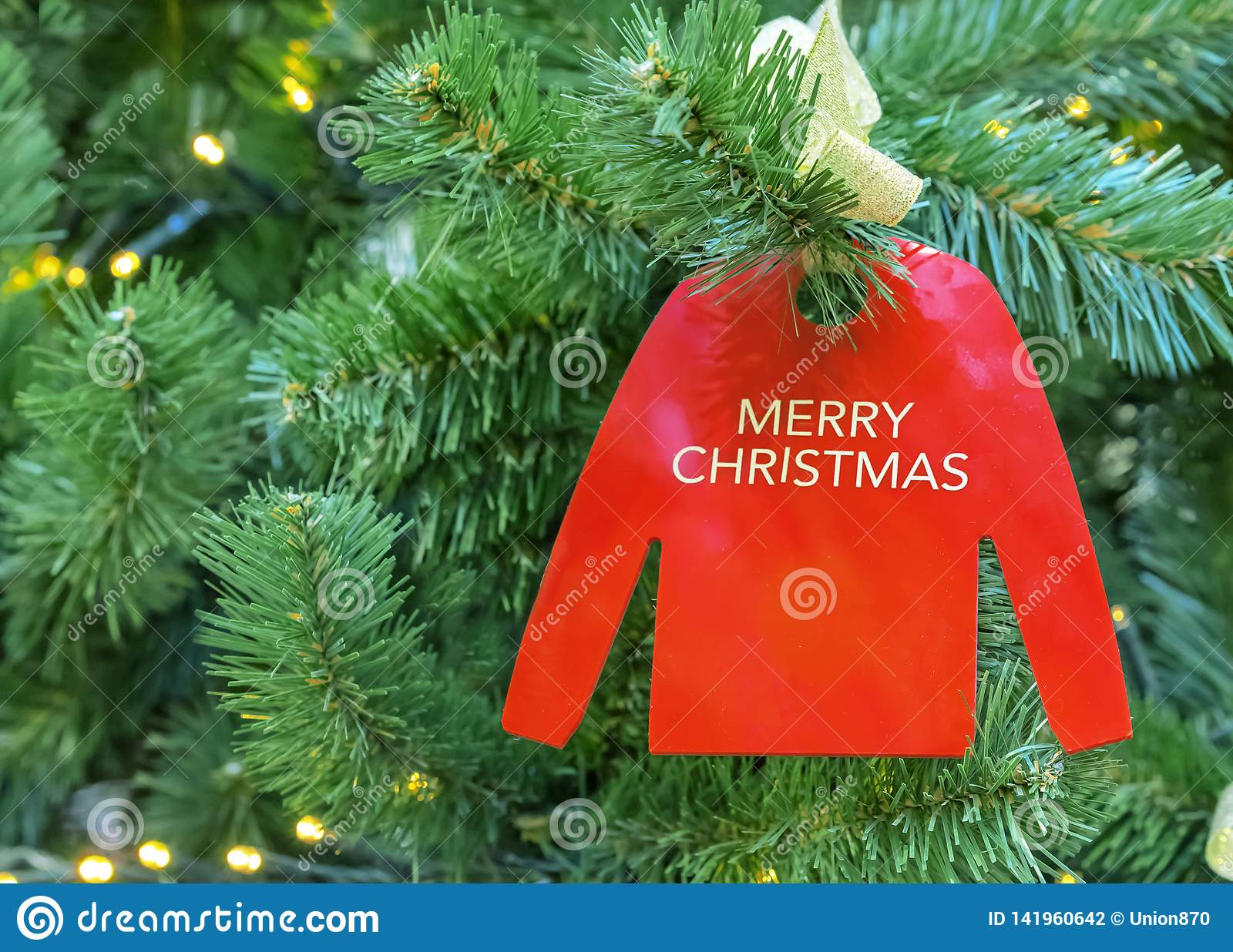 Ornament on a Christmas tree in the form of a red jumper with an inscription Merry Christmas