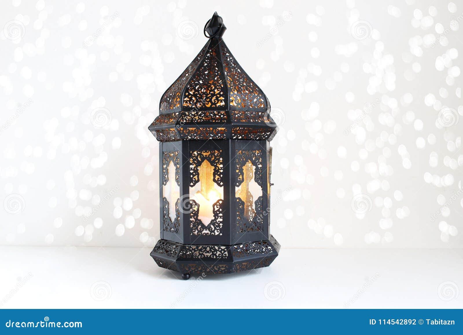 Ornamentacyjny ciemny marokańczyk, Arabski lampion na białym stole Płonąca świeczka, błyskotliwi bokeh światła Kartka z pozdrowie