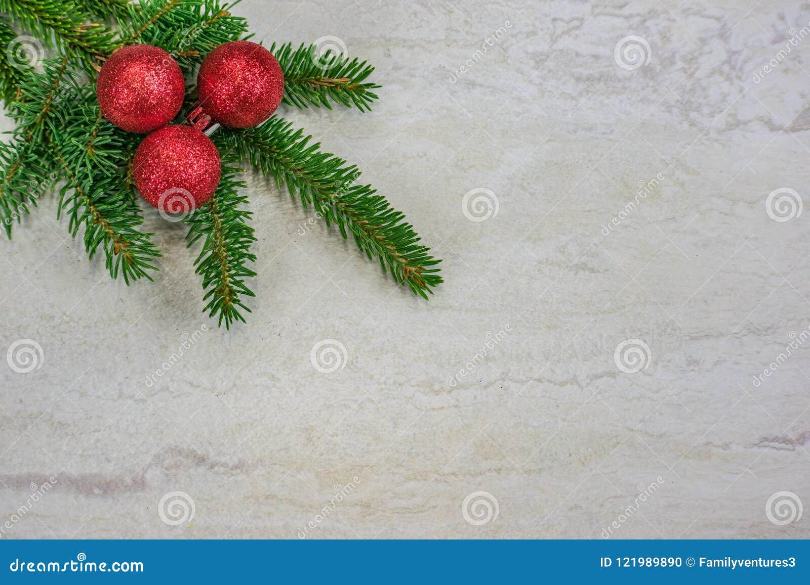 Ornamentos de la Navidad en una rama spruce con el espacio de la copia