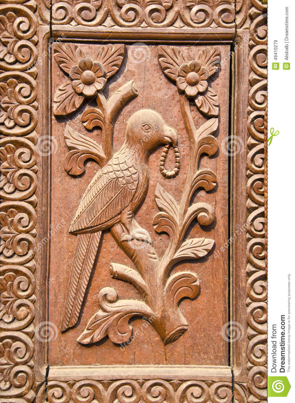 Ornate carved wood door fragment with bird relief stock
