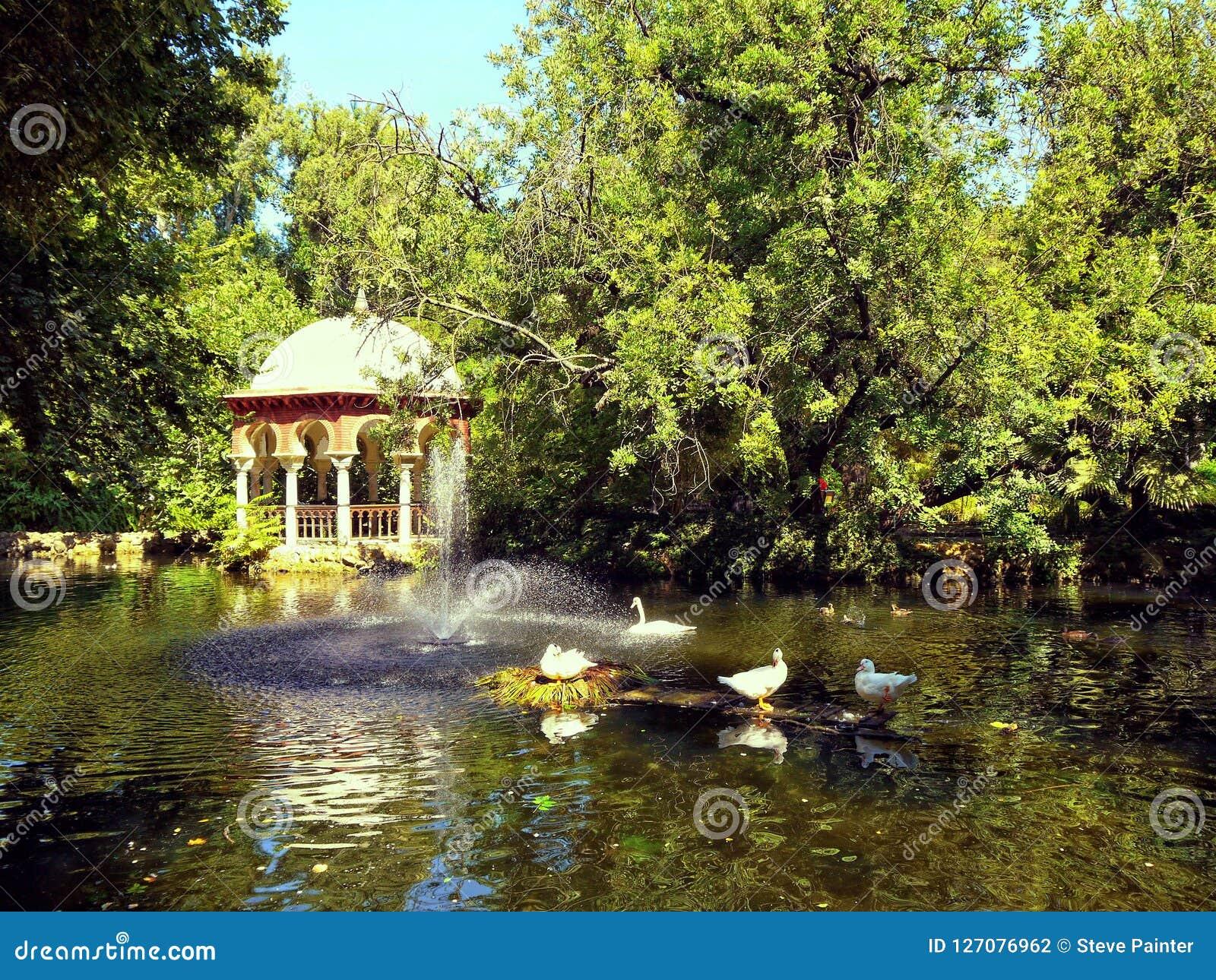 An ornate gazebo beside an ornamental duck pond.