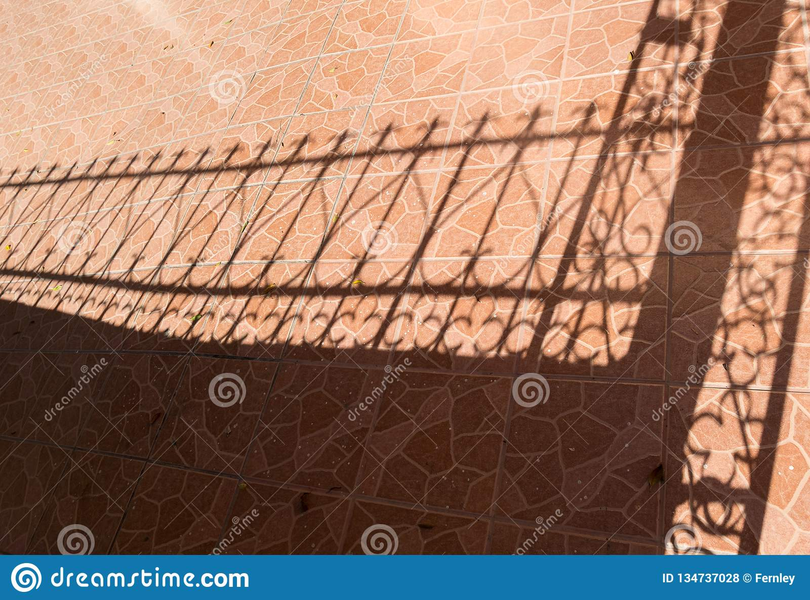 Tile floor and iron fence shadow