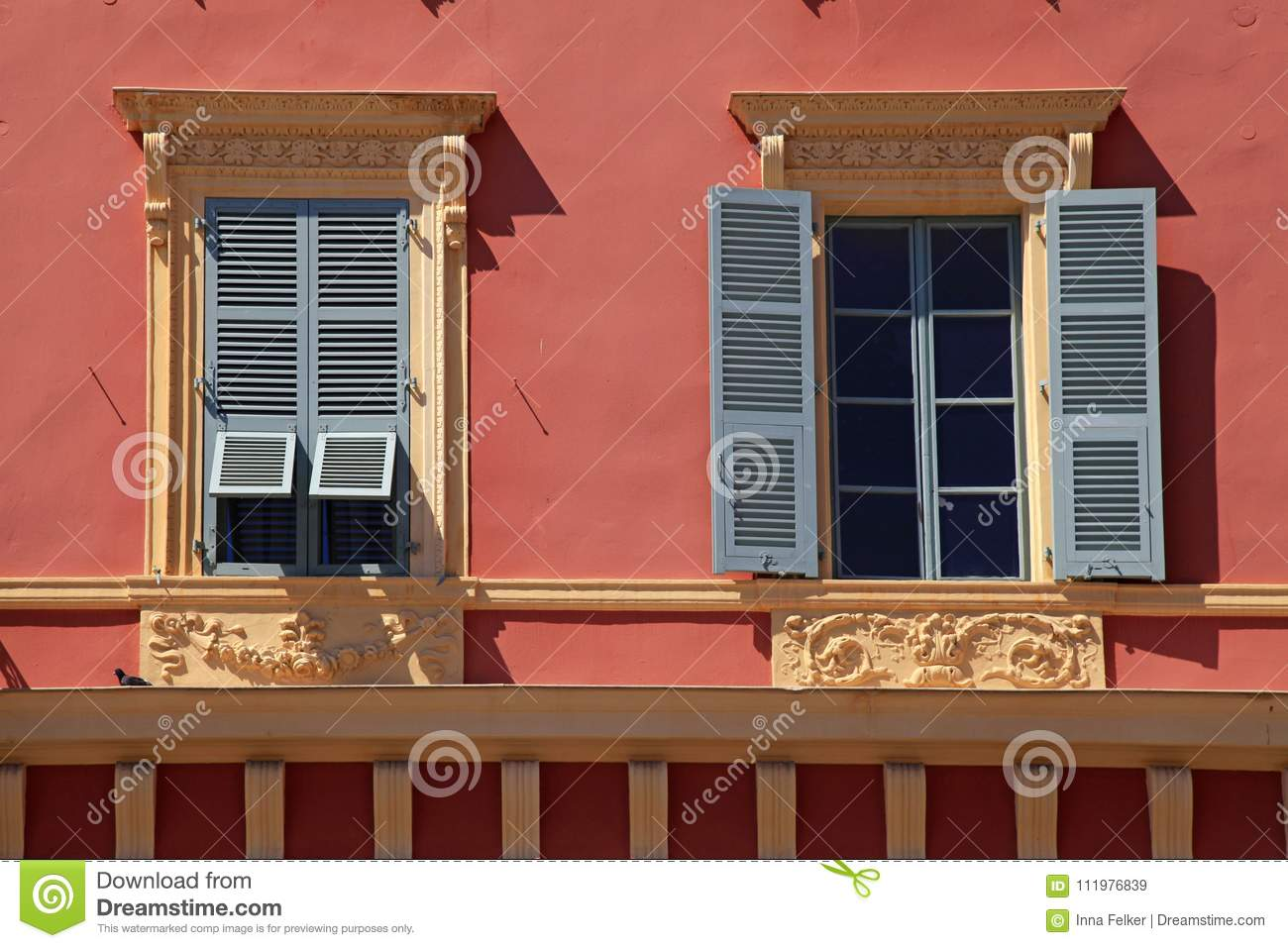 Ornate windows with grey shutters in old red stucco house, Nice, France