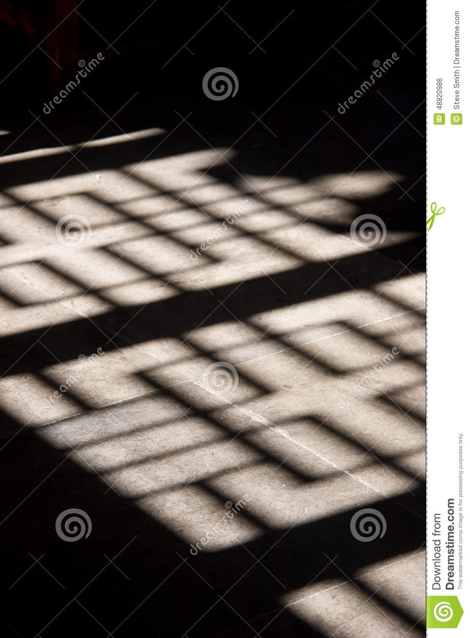 Ornate wooden screen casts interesting shadow on stone floor.