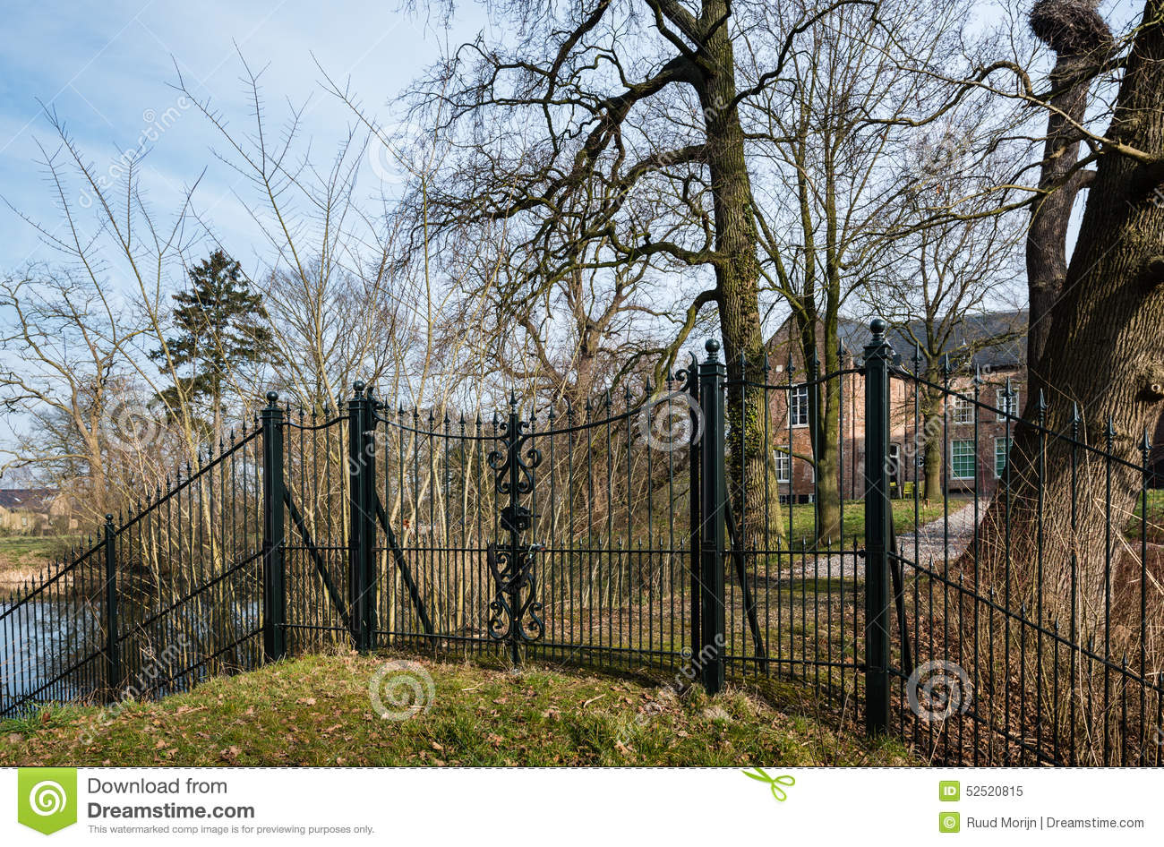 Ornate Wrought Iron Fence In Front Of An Old Country House