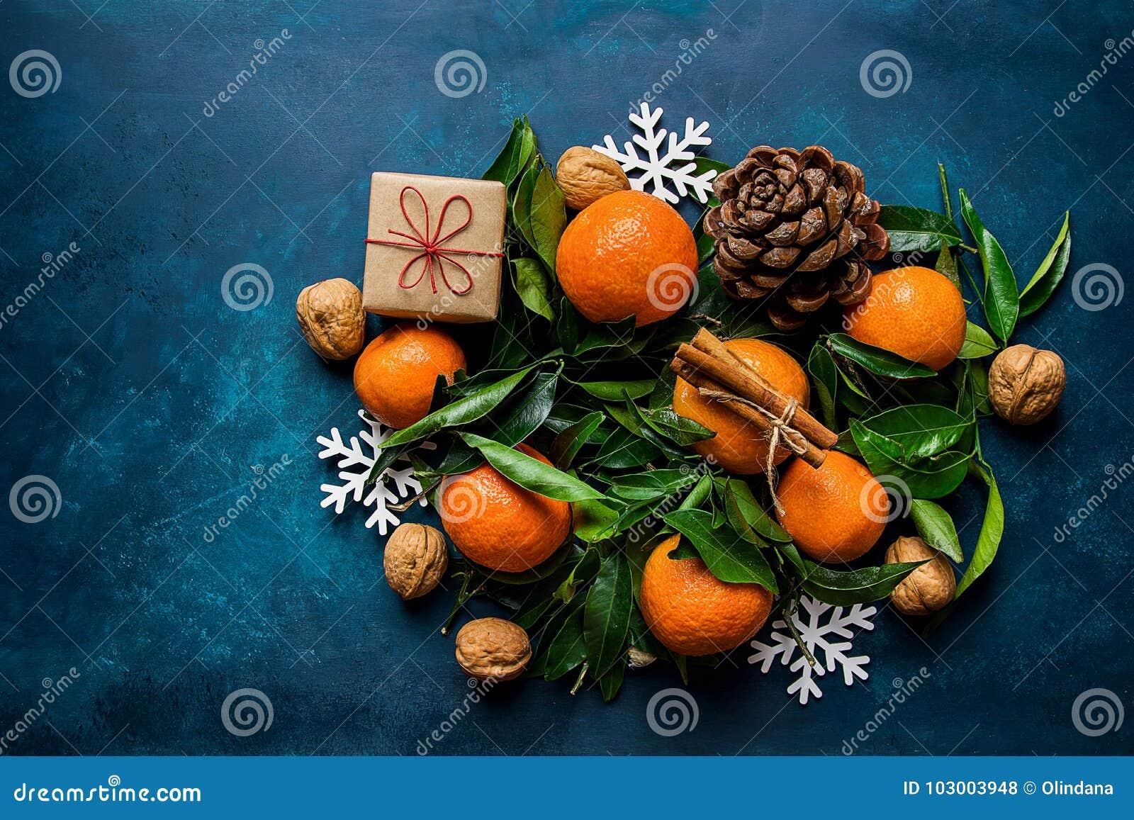 Ornements lumineux de flocons de neige de boîte-cadeau de cônes de pin de feuilles de vert de mandarines sur le fond bleu-foncé N