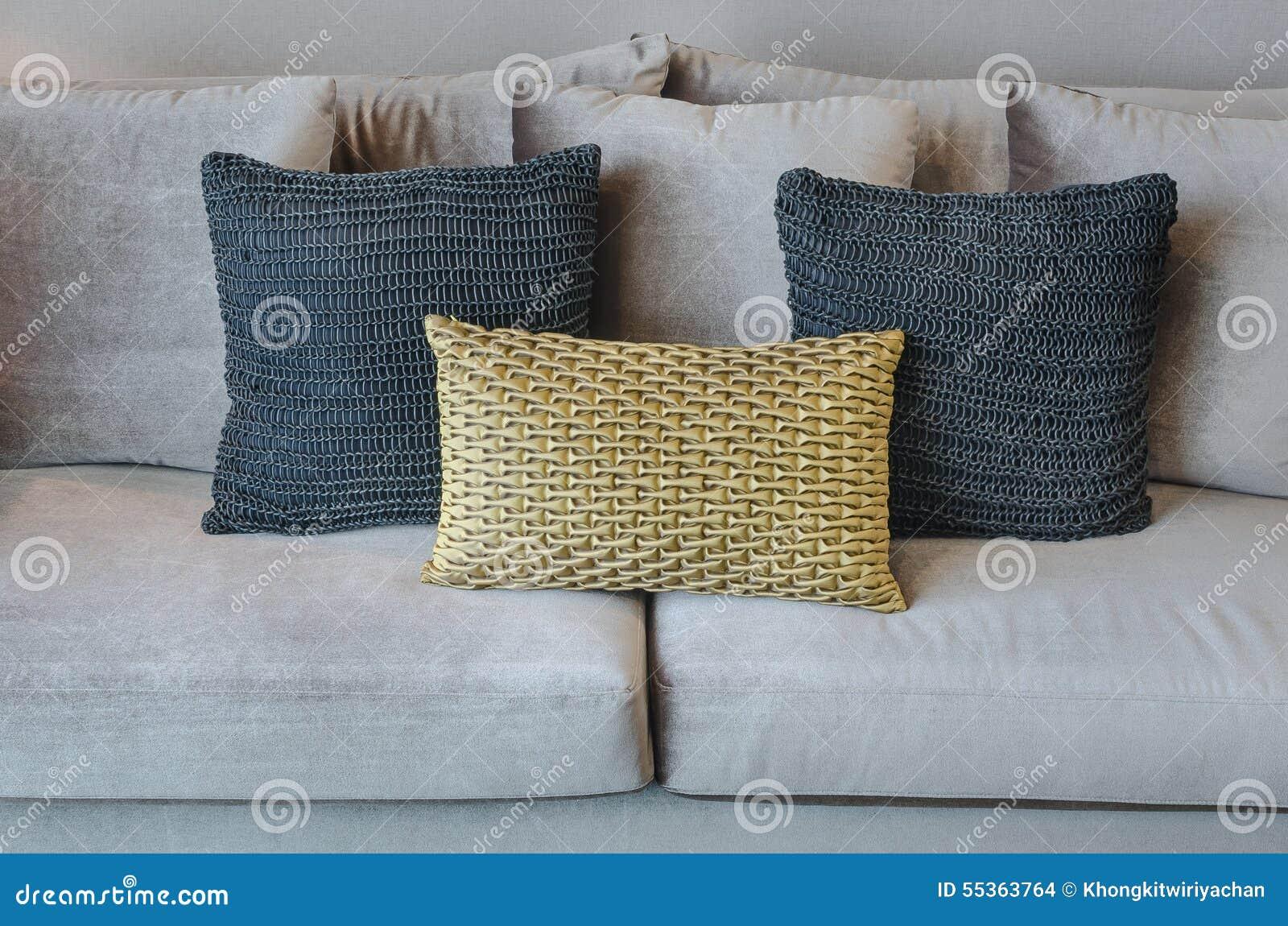 Oro e cuscini neri di colore sul sofà grigio