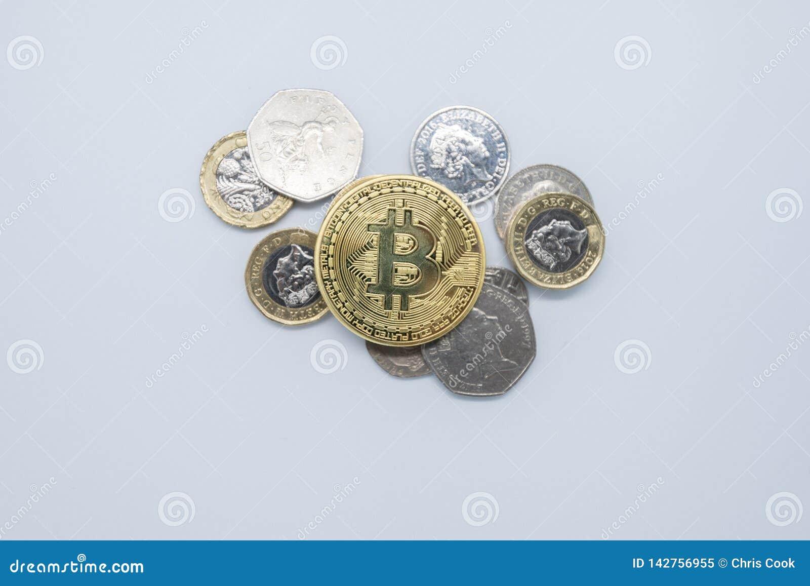 Oro físico Bitcoin que pone encima del dinero inglés viejo llano