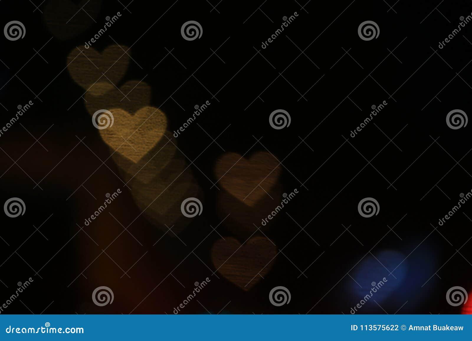 Oro giallo in forma di cuore su bianco variopinto del bokeh di