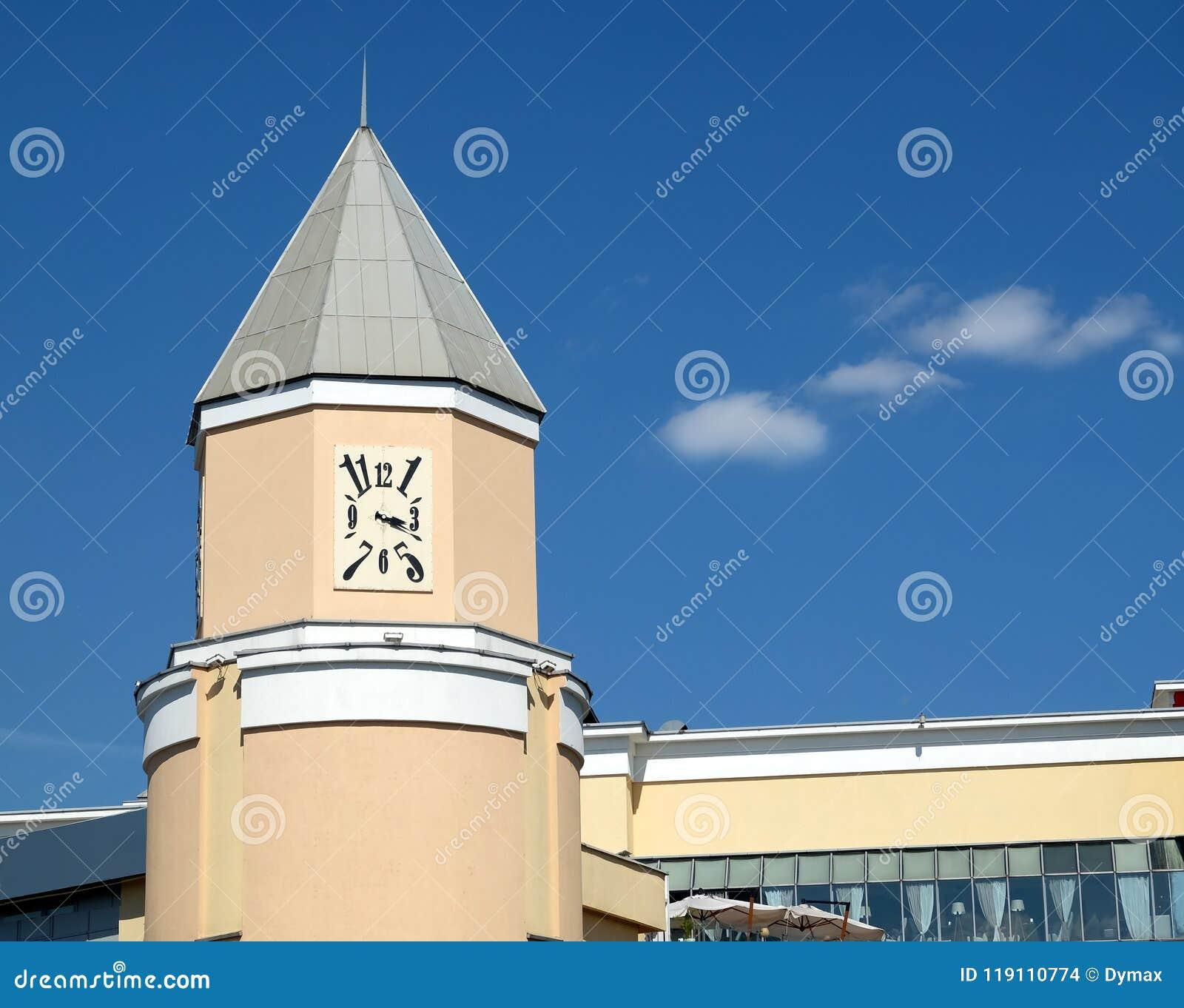 Orologi quadrati sulla torre sulla costruzione beige della città sotto il chiaro cielo blu il giorno soleggiato luminoso