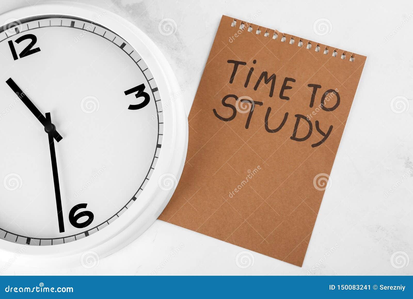 Orologio e foglio di carta con TEMPO dell iscrizione DI STUDIARE su fondo leggero Concetto della gestione di tempo