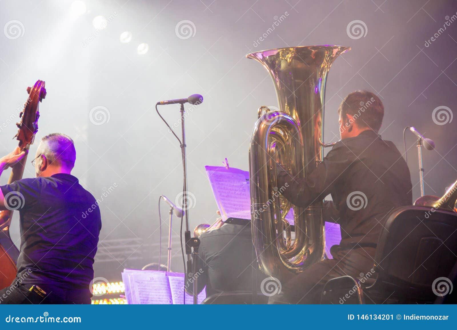Orquesta sinfónica en la etapa, sección de cobre amarillo de orquesta, detrás del lanzamiento de las escenas