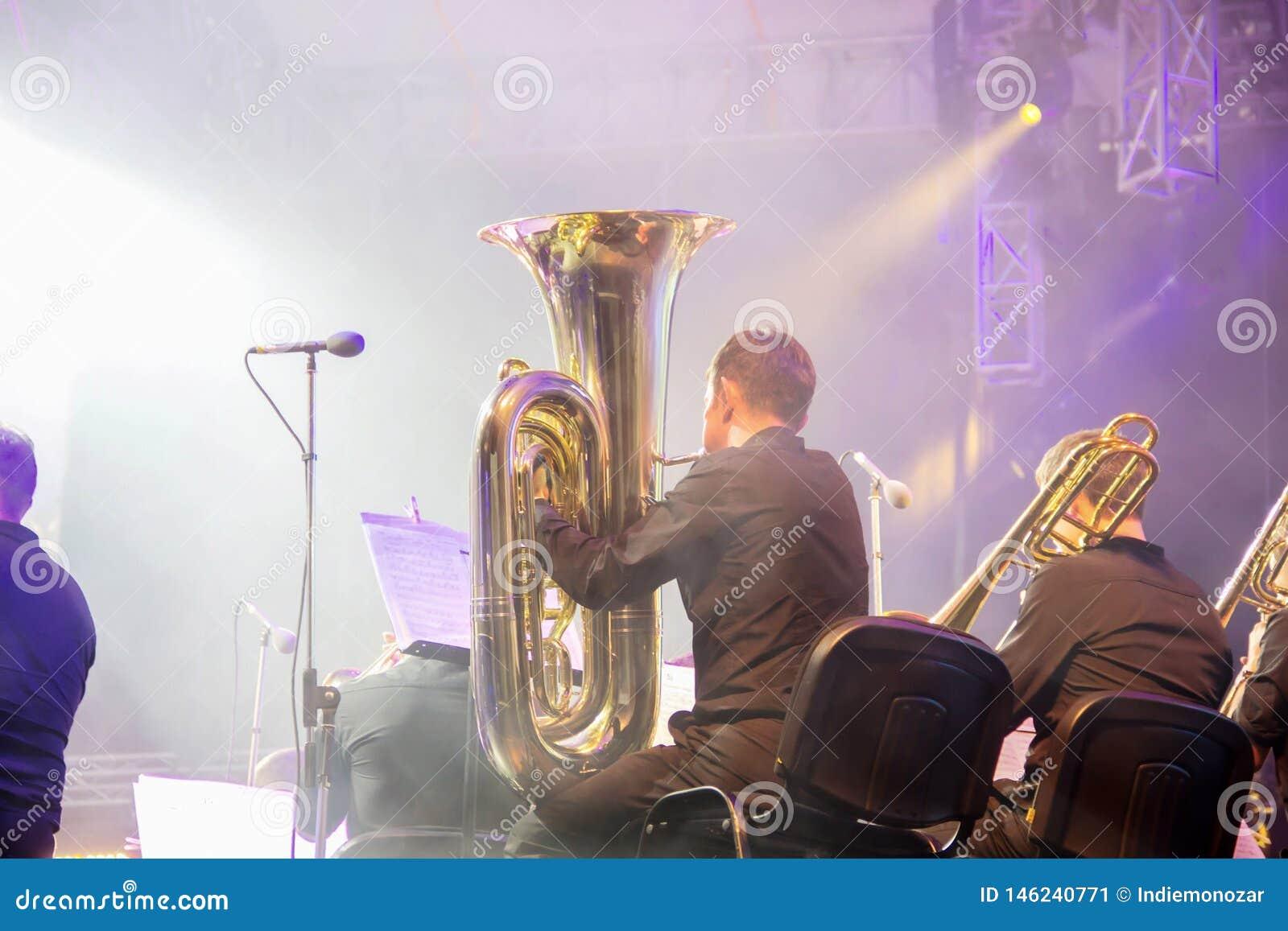 Orquesta sinf?nica en la etapa, secci?n de cobre amarillo de orquesta, detr?s del lanzamiento de las escenas Tubaist en soplo neg