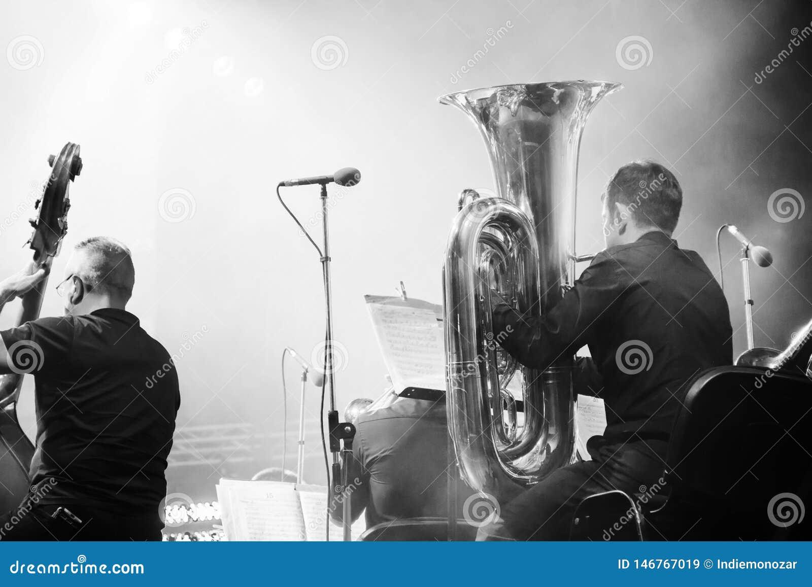 Orquesta sinf?nica en la etapa, la tuba y los bajistas dobles, detr?s del lanzamiento de las escenas en blanco y negro