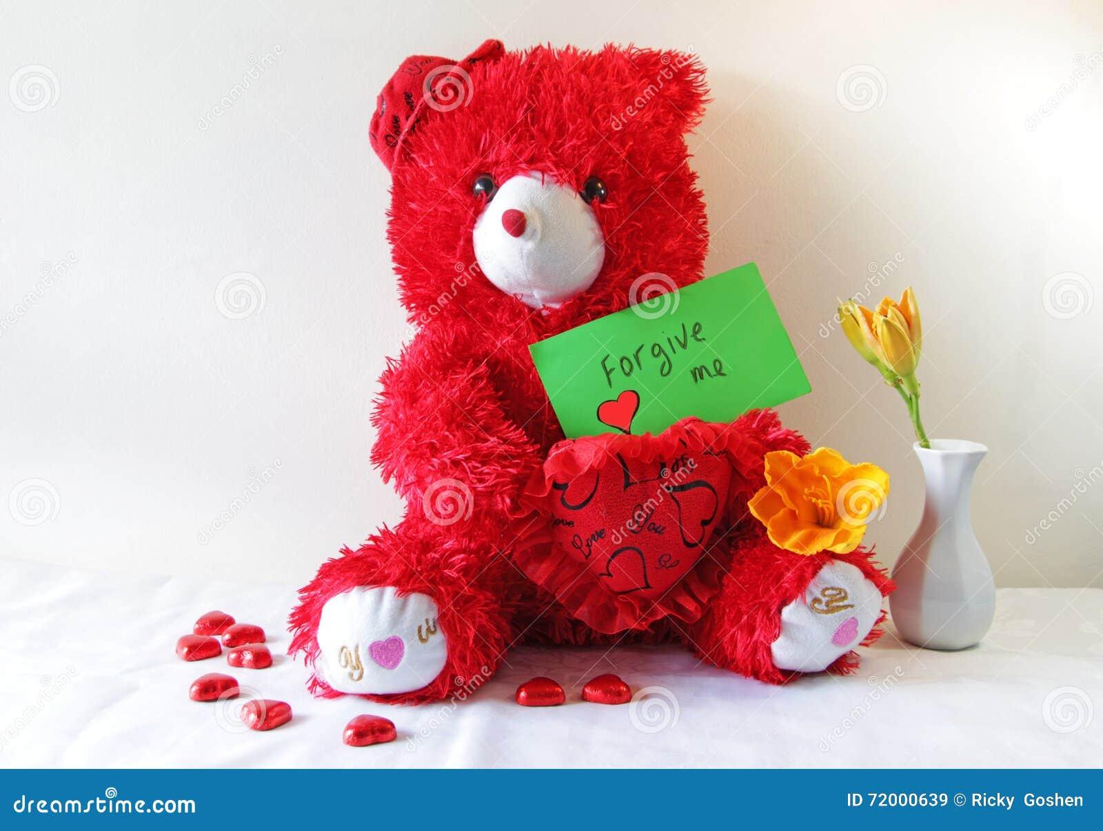 Orsacchiotto rosso che tiene un perdono me nota