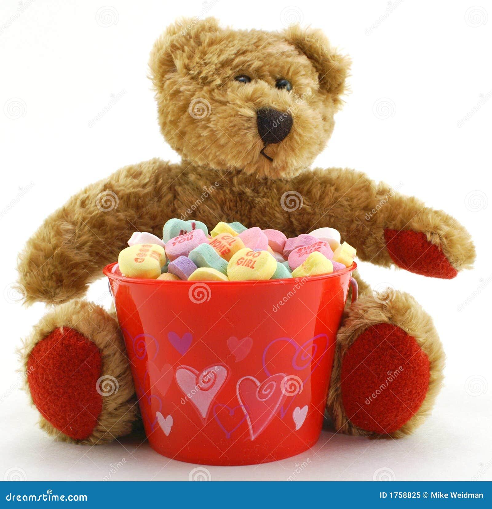 Orso di giorno del biglietto di S. Valentino con i cuori della caramella